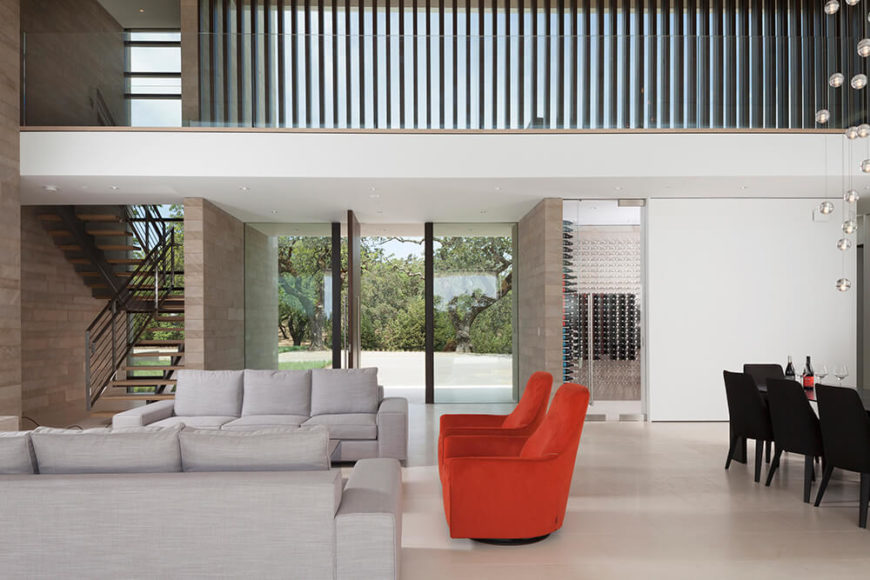 The great room is a massive, two story space with a bold mixture of modern furniture sharing an open-plan area. The upper floor hall flanks this space, separated only by an invisible expanse of glass balustrade.