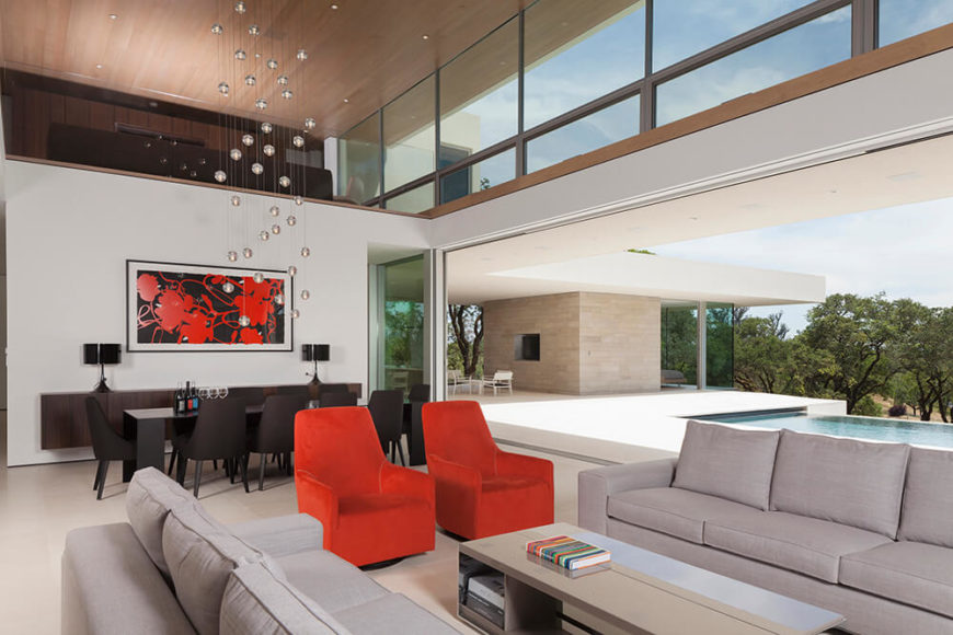 Moving into the home itself, we can fully appreciate the open design, erasing the boundaries between interior and exterior spaces. The great room features modern furnishings and a full dining room setup at left.
