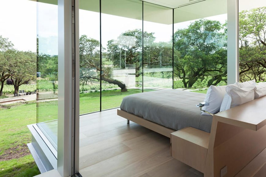 Here we see inside the bright and minimal guest house, with its bedroom treated to panoramic views of the landscape. Light natural wood, steel, and glass comprise the sleekly connected elements.