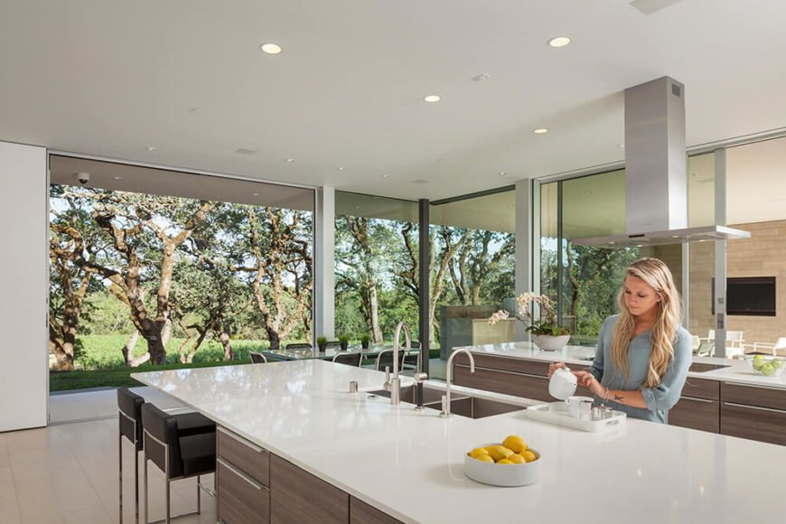 The vast kitchen is entirely wrapped in glass, with a massive sliding panel opening to connect the room to the outdoor sheltered space. Rich wood cabinetry is contrasted by glossy white countertops on a pair of large islands.