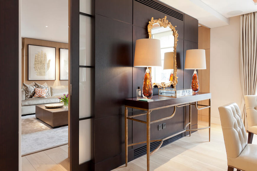 Divided from the living area by sliding shoji doors, the dining room is backed by a dark timber feature wall at center. A side table with matching wood tone stands in front, topped by an elegantly framed mirror.