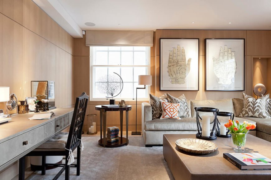 The living room enjoys a smorgasbord or intriguing elements throughout its sleek wood panel enclosed space. Artwork on the walls complements a large slab-like coffee table, while a built-in floating desk design meshes perfectly with the neutral walls.