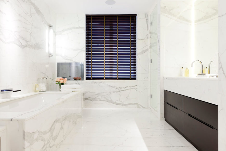 Here's more of that rich Carrera marble, flush throughout the bathroom from the walls to the bath surround. Dark wood cupboards below the vanity add a splash of contrast.