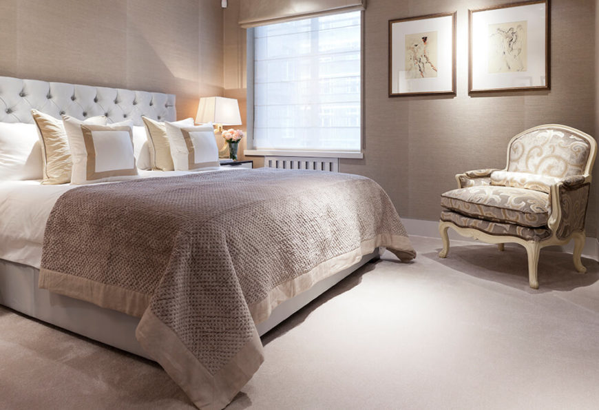 The second bedroom is wrapped in a more neutral dark beige tone, accentuating the traditional elegance of the carved wood armchair and button tufted headboard.