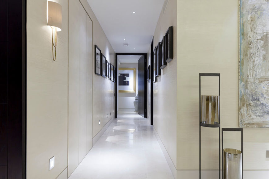 Moving down the main hallway from the open-plan central space, we see the expansive white flooring lit via subtle low wall lights, with the entire neutral space lined with black-framed artwork.