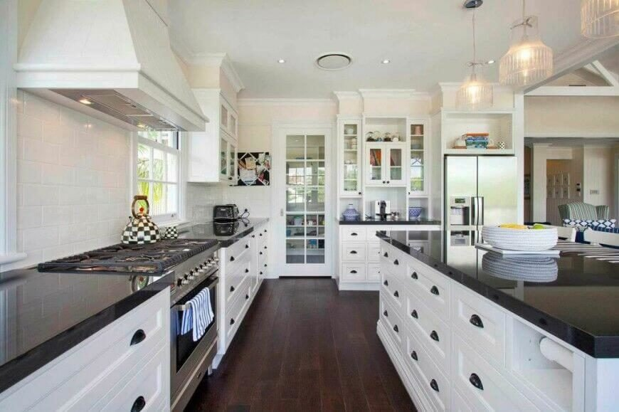 This gorgeous contemporary kitchen utilizes dark granite counter tops and wood flooring to break up the use of bright white. Glass fronts on the upper cabinets and window panes in the pantry door assist this purpose and allow pops of accent colors to show from the inside. The highly reflective surface of the counters keeps them from feeling to heavy in such a light space.