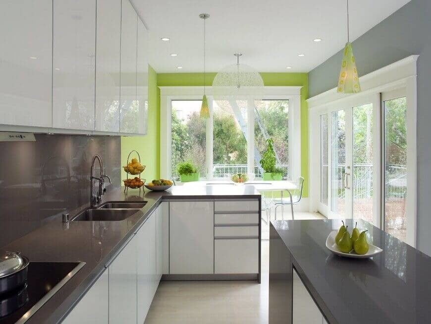 This color scheme of white, grey, and bright green differentiates this kitchen from others of the same contemporary style and keeps the bright white cabinets from overpower the rest of the room. Keeping the high-gloss finish of the cabinets and counters the same throughout the kitchen helps to reflect the light from the large windows further into the room.