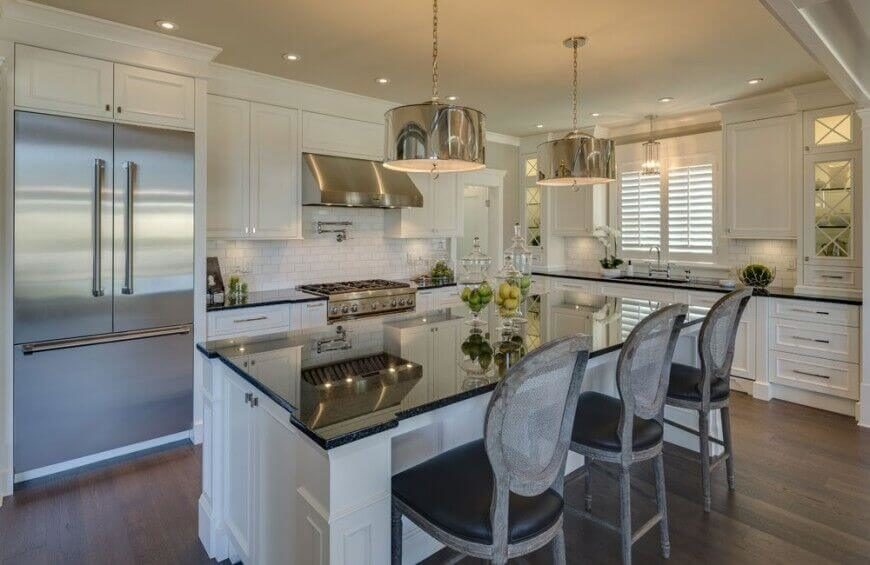 This beautiful kitchen makes great use of reflective surfaces to add interest and brighten the room. The dark counters and barstools bring weight to this broad room and complement the striking wood floor. The white cabinetry and tile backsplash keep the room feeling open and airy.