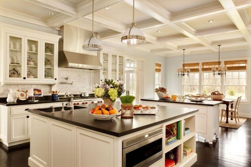 This impressive kitchen has a lot going on. The beautiful wood floors complement the granite countertops and bring depth to this airy room. Glass-fronted doors separate the white of the cabinets while the decor adds bright pops of colors. The powder blue walls keep the kitchen light and open while adding additional color to the room. Similarly, the recessed ceiling squares bring visual interest to even the top of the room.