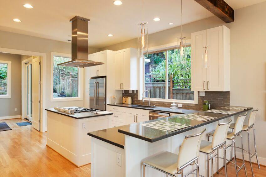 This beautiful, bright kitchen utilizes the white and grey color scheme that is popular in contemporary kitchens. The sleek cabinets complement the clean edges of the appliances and granite countertops. The light grey subway tiles add texture and interest to the space while the light wood floor brings warmth to the room.