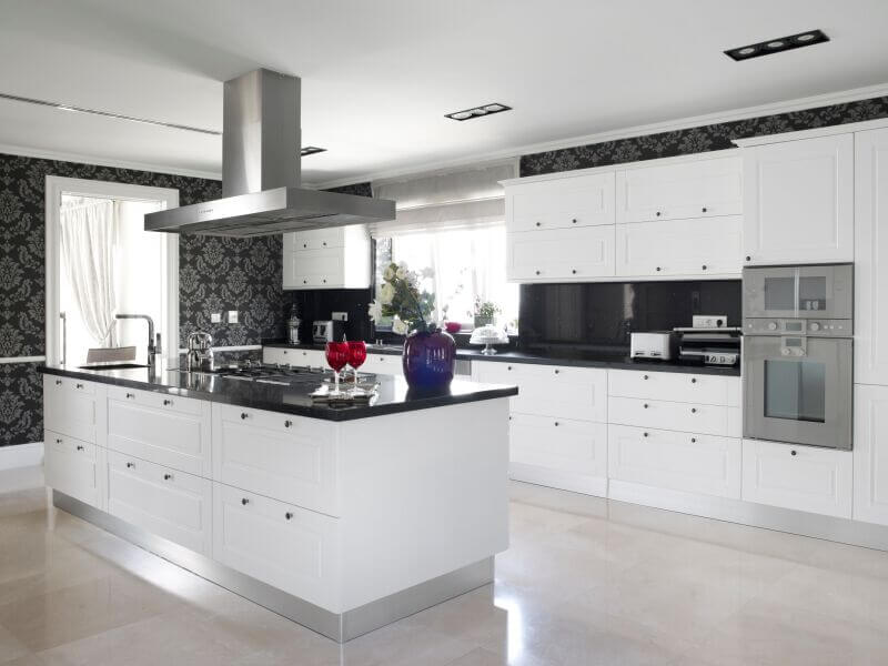 This striking, contemporary kitchen utilizes black counters and bold accent wallpaper to break up the use of white in the room.