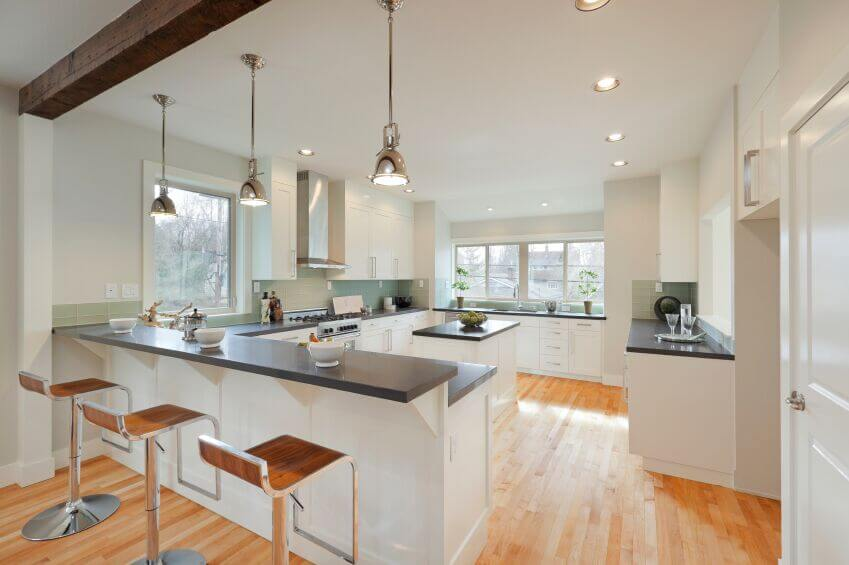 The same kitchen from a different angle, this view shows off the true expanse of the countertops and the use of windows and light in the space. The rough, exposed beam along the ceiling adds interest and draws the eye up to the high ceilings.