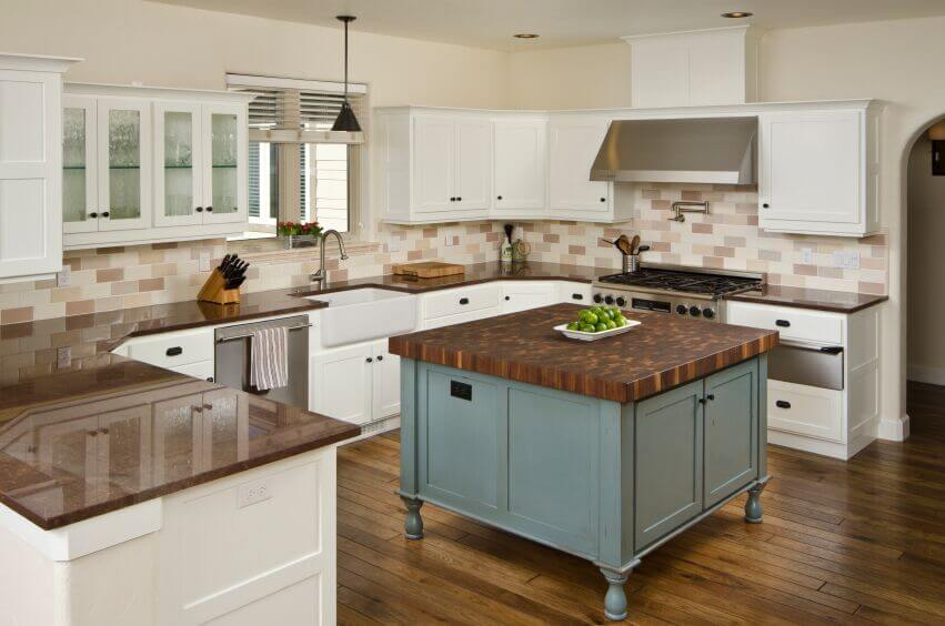 These stunning wood floors are complemented by the island countertop and the chocolate brown granite. The warm palette is continued in the tile backsplash and, in this case, the white cabinets are used to break up the warm tones of the room. Meanwhile, the lovely blue of the island base brings a cool accent color and complements the use of brown.