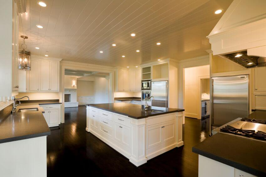 The glistening dark wood floor of this kitchen brings out the dark granite. Balancing this expanse of floor, white cabinetry and walls keep the dark wood from overpowering the room and ensure the room stays open and bright. Shiny, stainless steel appliances and matching fixtures help to brighten the room. Using white wood paneling on the ceiling is an interesting switch from a standard flat white ceiling.