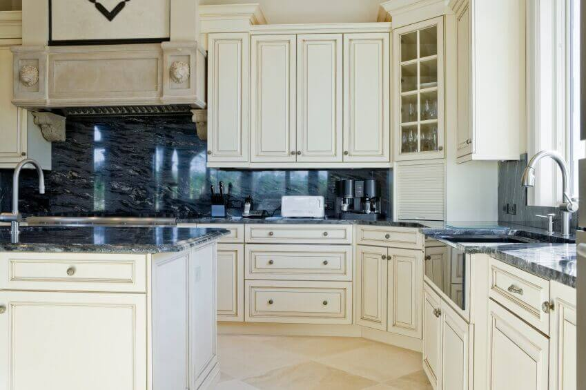 This lovely kitchen uses the same beautiful granite for not only the counters but the backsplash too, an excellent example of balancing the lightness of the room without having dark flooring. The gorgeous cabinet fronts keep the use of white interesting and match the lovely floor.