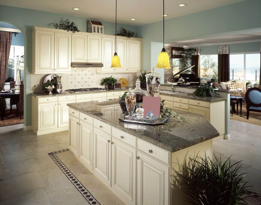 These stunning granite counters go well with the off-white cabinetry and powder blue walls. Accent tiles are pulled up into the room from the floor around the island and into the backsplash behind the stovetop. The kitchen maintains the rich feel of the rest of the house visible in the background.