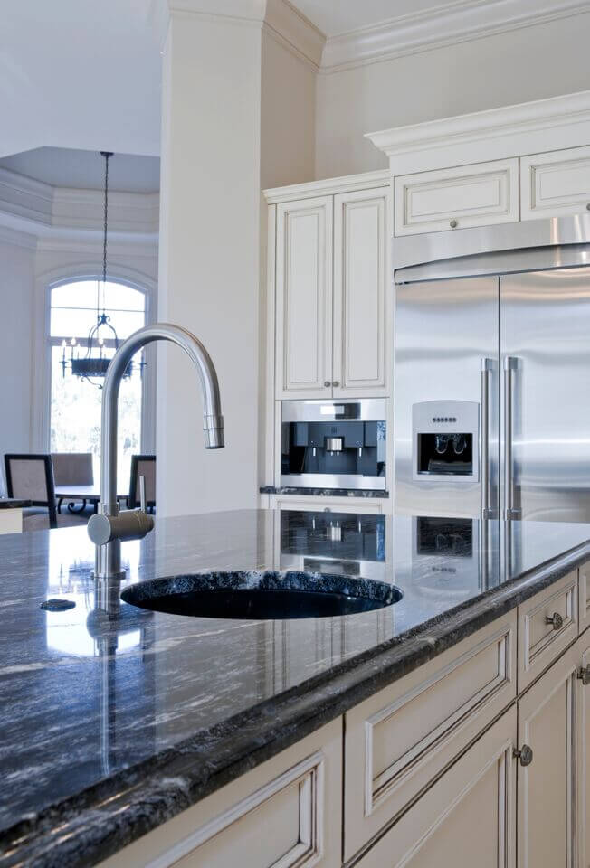 Here is a better angle of the use of stainless steel to accent this luxurious kitchen. The gorgeous lapis blue of the granite can also be seen here. Using a dark colored of granite is a great way to pull accent colors into the kitchen without needing the counter-clutter of decor.