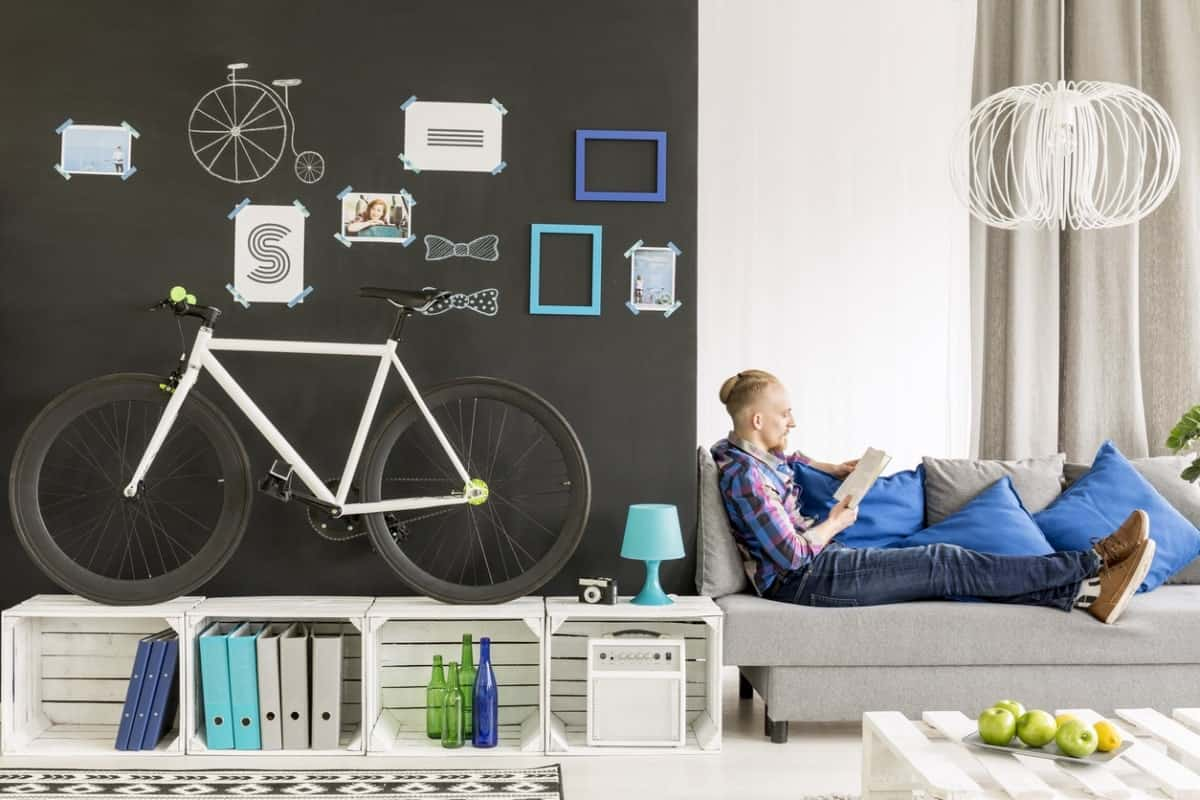 A bicycle is displayed on a crate shelves and against a black accent wall in the living room with a man sitting and reading on a couch.