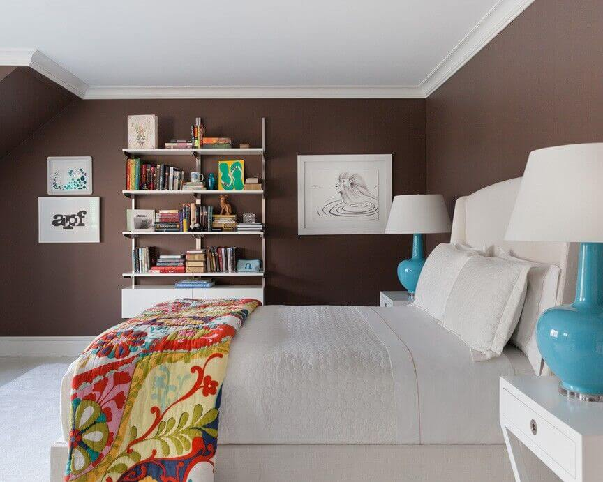 High contrast informs the look of this bedroom, with pristine white furniture set against chocolate brown walls. The bed is flanked by a pair of white side tables, while the white bookshelf across the room continues the theme.