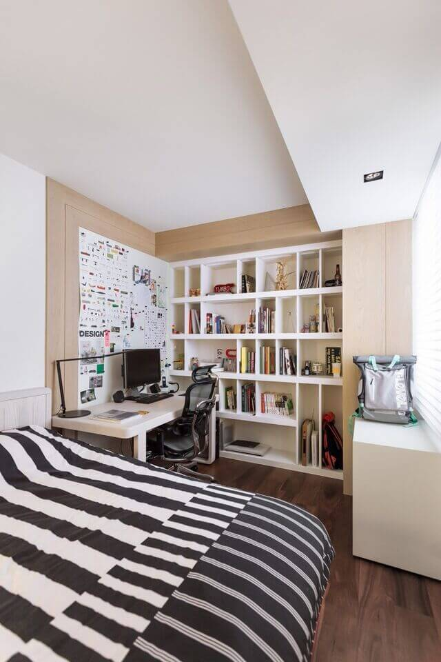 In this cozy white space, we see the warming contrast between rich natural hardwood flooring and white walls. The far wall is entirely taken over by built-in shelving with asymmetrical compartments.