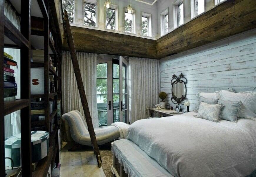 This rustic luxury bedroom features aged wood and exposed beams below a set of wraparound windows. The massive natural wood bookshelf spans toward the ceiling, with a built-in rolling ladder for ease of access.