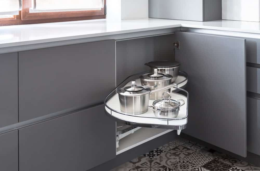 A kitchen corner storage is pulled open to reveal the stainless steel pots it contains inside.