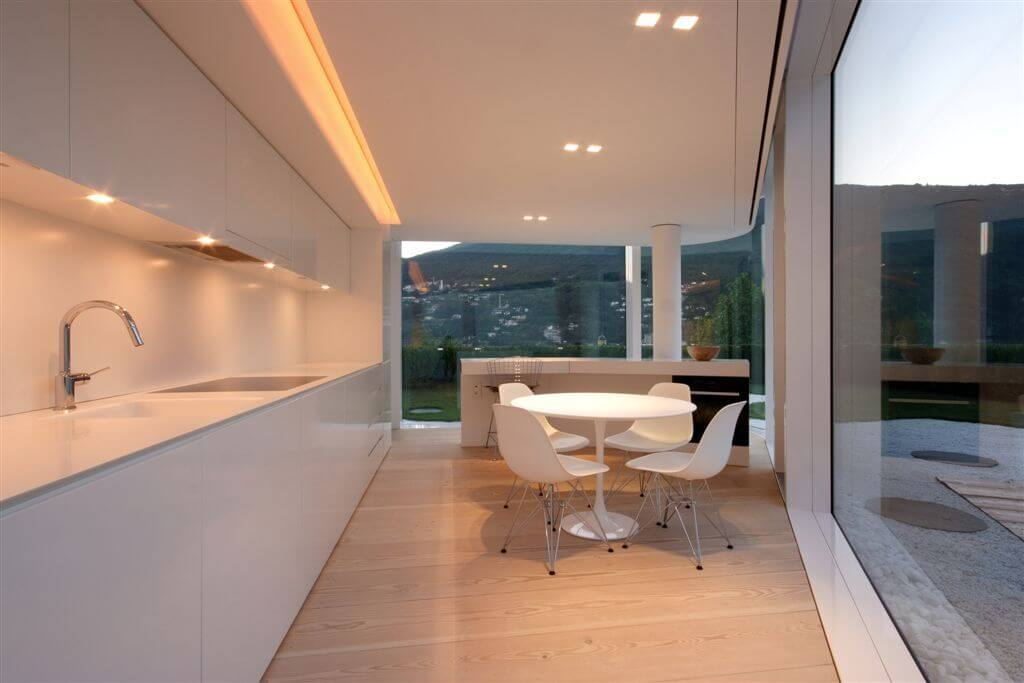 In a sleek, ultra-modern home wrapped in full height glazing, the kitchen is defined by a pair of lengthy white countertops, framing a triangular expanse of natural hardwood flooring. A white circular dining table rests at center.
