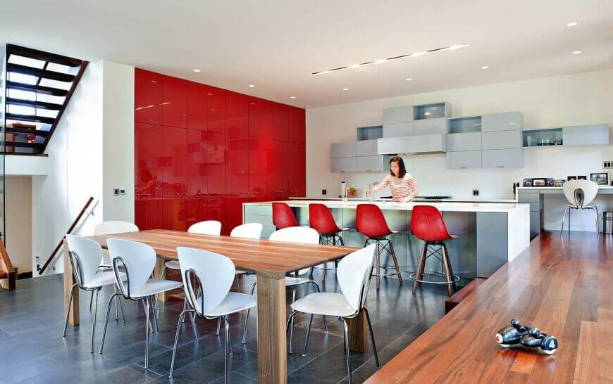 High-end modern kitchens often appear in sleek whites and blacks, but this open-plan design aims to wow with a solid red wall of glossy cupboards and matching red seating at the island. A massive natural hardwood dining table stands in the foreground.