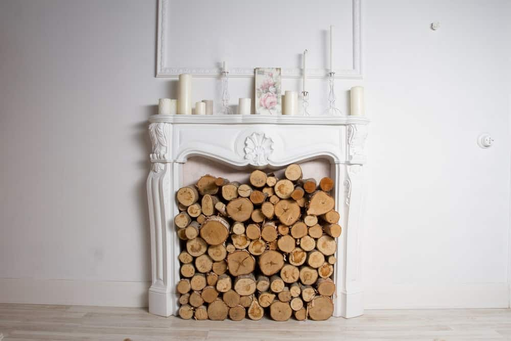 Firewood stored to the brim in a white fireplace with candles of different sizes on the fireplace shelf.