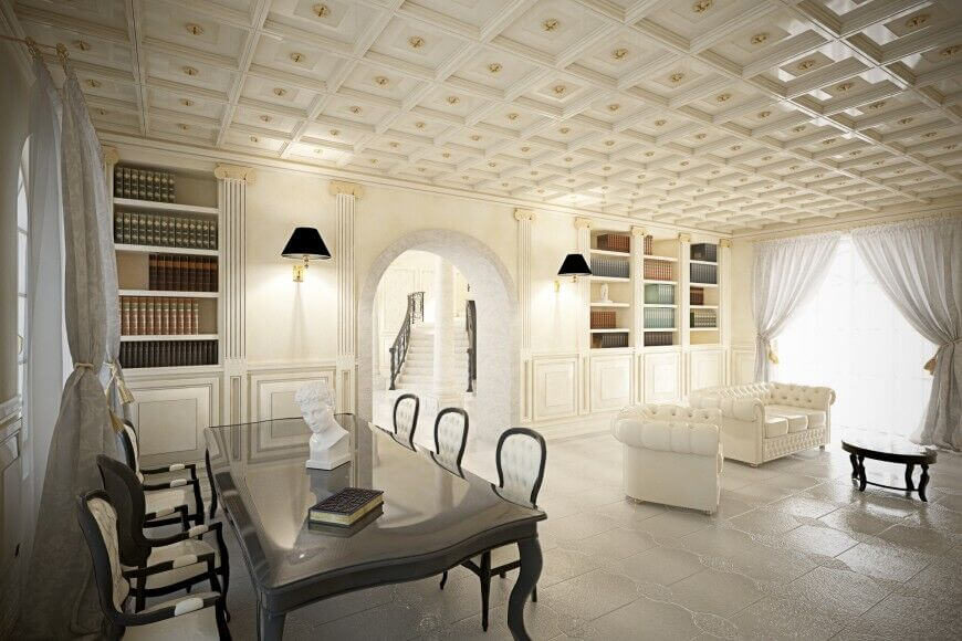 This incredible white elegant living room features textured tile floors and a coffered ceiling, where each section has a small golden medallion. To the right is a seating area featuring white leather button-tufted furniture, while to the left is a small meeting area with bookshelves.