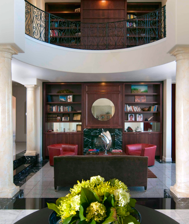 A massive curved two-story library and living room features a rich modern-style dark chocolate leather sofa paired with two more contemporary red leather armchairs, one on either side of the fireplace.