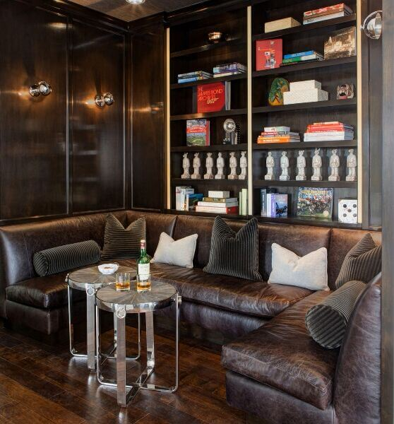 A C-shaped genuine leather sofa sits in a small dark wood nook with built-in shelves. The sofa is paired with two stainless steel side tables.