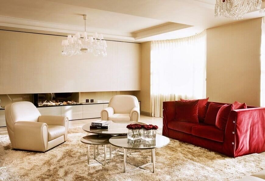 A single rich red sofa adds bold color to this otherwise white living room, and is paired with two sleek white leather armchairs and a tiered mirrored coffee table. Two unmatched chandeliers hang above the room in tray ceilings.
