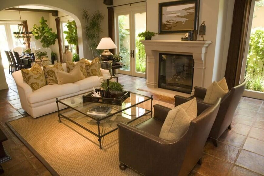 In a living room that is a crossroads between other rooms, it can be difficult to create an intimate area for conversation to welcome your visitors to. Since the fireplace is situated between two sets of French doors, it only makes sense to pair a loveseat with two chairs. In this case, the leather is paired with a soft white cloth loveseat and a glass coffee table.