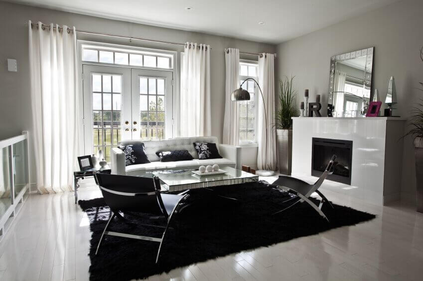 An incredibly stark white living room with French doors leading to a terrace. Paired with the white contemporary couch are two sleek chrome and leather armless chairs. Soft, sheer white grommet curtains frame the windows and French doors.