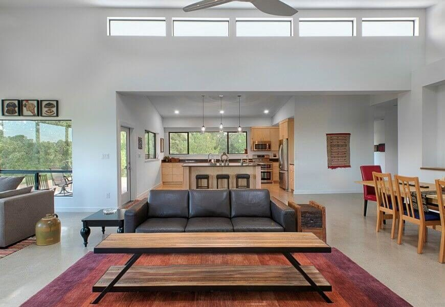 Small pops of color draw the eye around this large, open-concept living room. The colors in each spot are complementary, allowing the eye to flow from area to area.