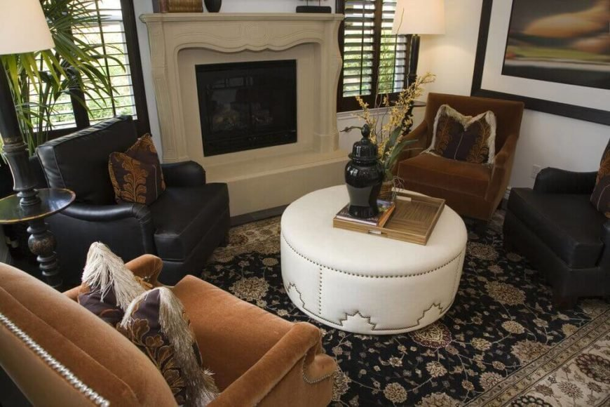 The seating arrangement in this more modestly-sized living room has a much more intimate atmosphere. Instead of a large sofa, four chairs are arranged around a white ottoman with nail-head detail. Two of the four chairs are a rich, dark leather, while the other two are a brown velour.