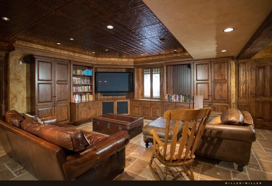 This family room features a darker leather sofa and a lighter armchair paired with an old leather-bound trunk as a coffee table. Even the tiled ceiling has a bit of a leather-like sheen to it.