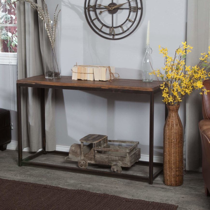 A distressed metal frame is topped with reclaimed wood, creating a rustic table with an industrial cast to it. The bottom of the table is entirely open, and perfect for storing a large accent item, like the truck in the image below.
