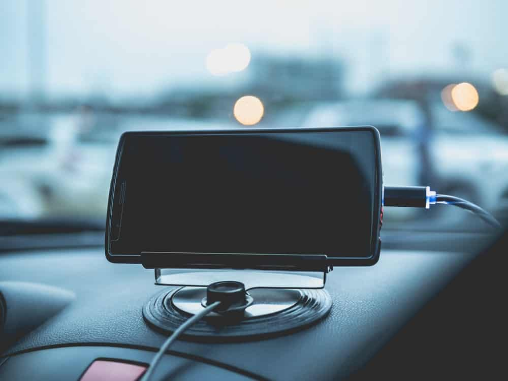 A mobile phone is held in place by a mobile storage device in front of the driver's seat.