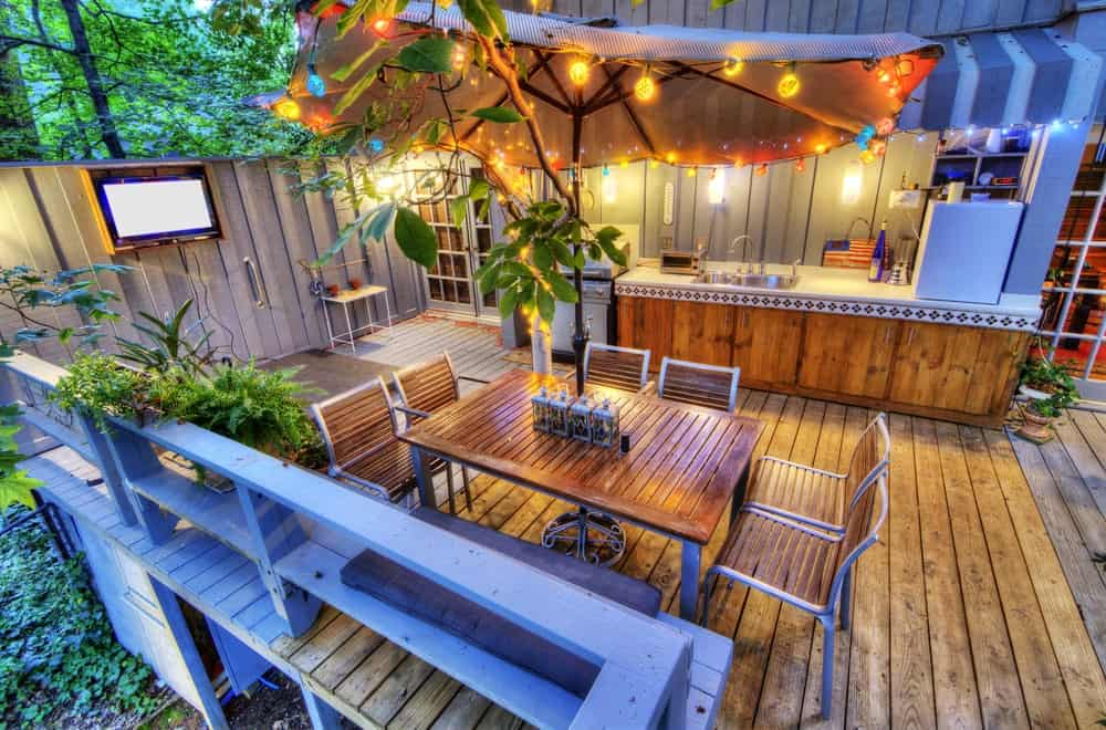 Deck with patio umbrella on an outdoor dining and kitchen with wall-mounted TV, outdoor wall lighting, and wood cabinetry.