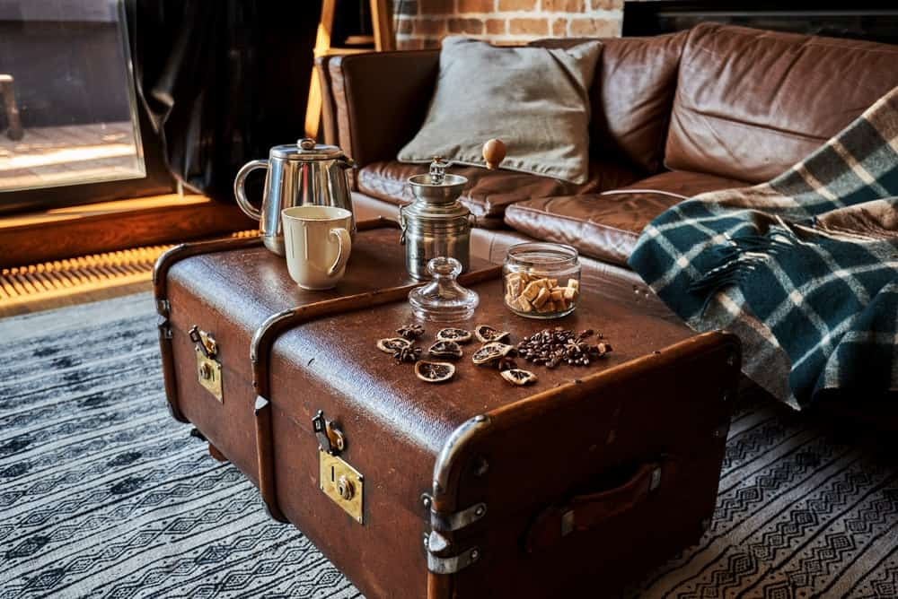 A chocolate-colored storage trunk used as a coffee table in the living room with a matching leather sofa and an area rug.