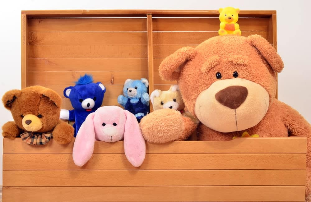 Different stuffed animals in an open wooden chest.