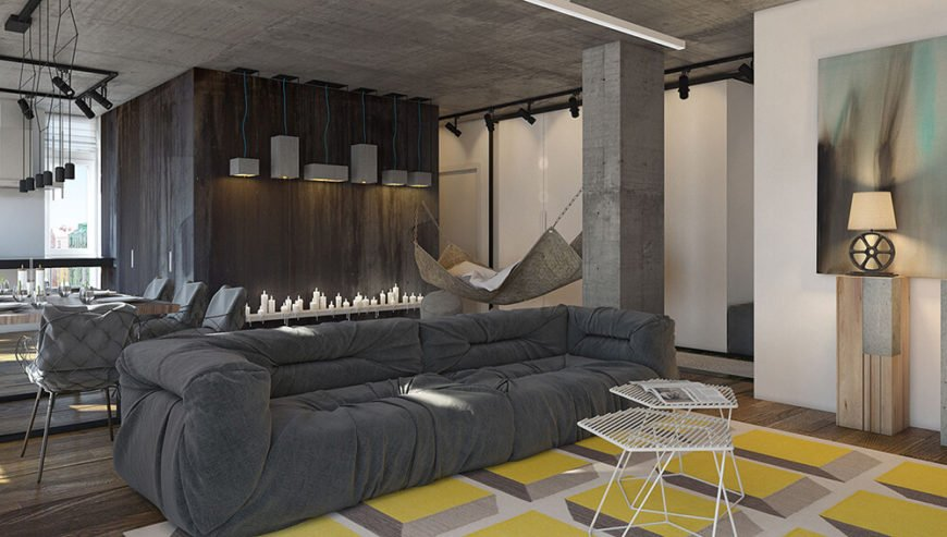 Color is brought into the living room by way of the complementing area rug. The use of hardwood floors softens the concrete pillars and ceiling while the plush grey couch looks comfy and inviting.