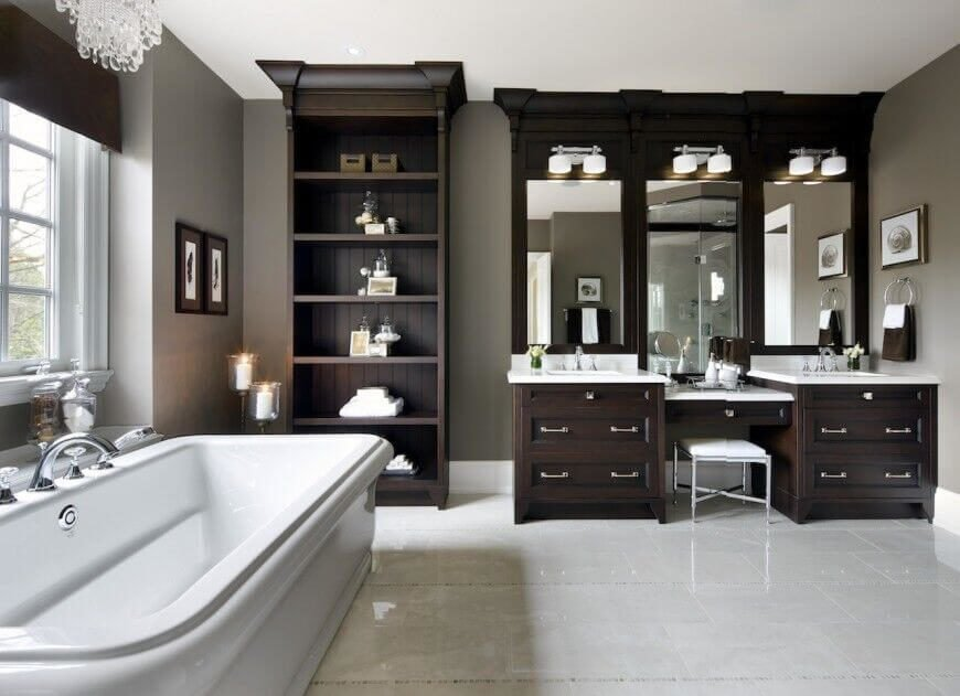 This bathroom's rich dark wood vanity extends from the wall and features ultra-deep cabinets for plenty of storage. The bathroom boasts three mirrors: one above each sink, with a third above the center makeup vanity between.