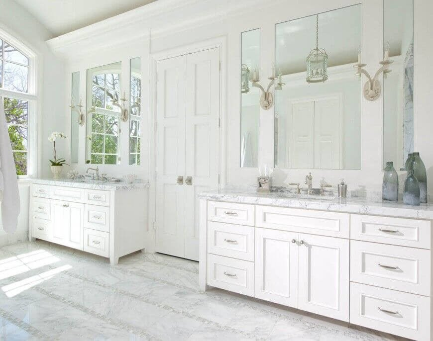 This pure white bathroom features two large mirrors on either side of the double doors, each framed by two narrower mirrors. The effect is stunning and incredibly elegant.