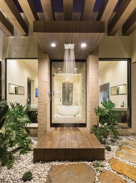 This incredible bathroom features a shower enclosure made to feel as though it were an outdoor shower. Through two large seamless windows we can see lengthy mirrors on both sides of the main bathroom.