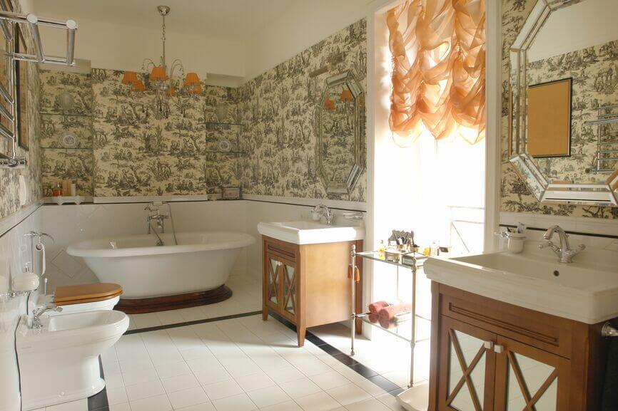 The mixture of sage green wallpaper and billowy, elegant curtains in a pale peach is an interesting combination for certain. Dual octagonal mirrors even have mirrored frames, which allows them to nearly blend into the walls themselves.
