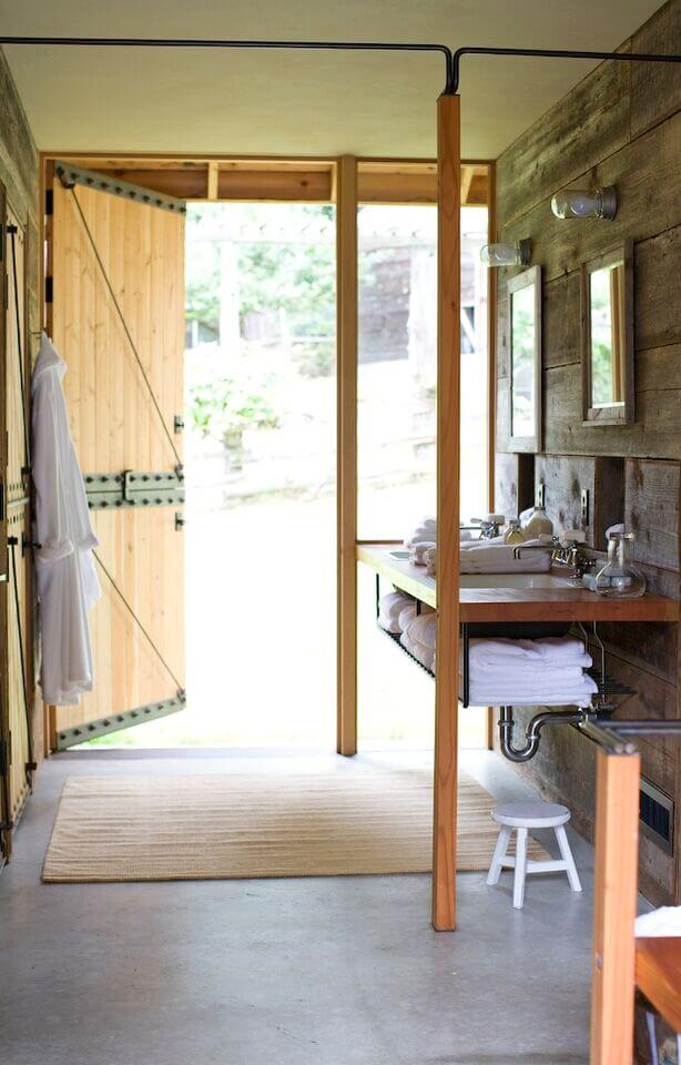 A rustic bathroom with a reclaimed barn door that leads directly outside of the home. This space is perfect for those with an active outdoor lifestyle. Simple framed mirrors in different sizes hang above each of the two shallow sinks.