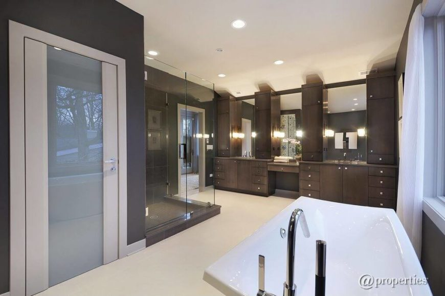 This enormous primary bathroom features an entire wall of vanities with plenty of storage for every bit of product imaginable. Mirrors top each individual vanity.